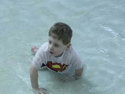 boy in a superman shirt in the pool